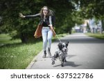 Stock photo young woman walking her dog on a street having troubles holding him on a leash 637522786
