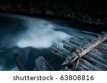 rapid flow of water under an old wooden bridge - stock photo