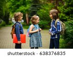 Small photo of Little school students briskly talk on the schoolyard. Children have a good mood. Warm spring morning. Behind shoulders at schoolmates schoolbags.