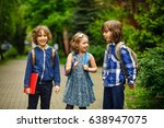 Small photo of Pupils of elementary school briskly and cheerfully talk on the schoolyard. Two boys and the girl have fun waiting for the beginning of occupations. Fine morning.