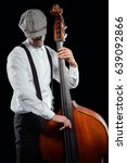 Small photo of Trendy musician playing bass, close-up. Looking down, wearing plaid flat cap, white shirt and suspenders, black background. Jazz, swing, blues, soul music.