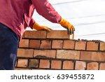 worker builds a brick wall in... | Shutterstock . vector #639455872