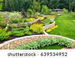 Natural landscaping panorama in home garden. Beautiful view of nice landscaped garden in backyard. Scenery of landscaping area in summer. Landscape design with flower beds. - stock photo