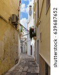 Small photo of Small alleyway decorated with colorful buntings in the historic center of Gallipoli, Puglia, Italy