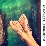 Small photo of Tanned well-groomed legs amid tropical turquoise sea . Pedicure and foot Spa .Perfect clean female feet . Spa ,scrub and care . Trotters jewelry , payal.