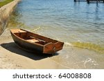 Small sailboat( pram) beached on shore against a seawall. It is used as a small transport to and from a larger vessel anchored in deeper water. - stock photo