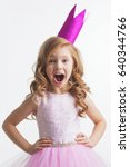 Small photo of Little princess girl in pink crown and beautiful dress on white background