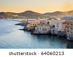 Houses along the sea on the island of Syros in Greece  at sunset. Classic architecture Greek islands. - stock photo