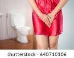 Small photo of Woman with prostate problem in front of toilet bowl. Lady with hands holding her crotch, People wants to pee - urinary incontinence concept