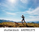 Stock photo man runs with his beagle dog on mountain top 640981375