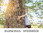 young asian girl hugging tree... | Shutterstock . vector #641066026