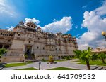 Small photo of Udaipur, India - October 3, 2013: The utterly romantic Udaipur City Palace with its beautiful landscaped garden pictured against a blue sky with clouds in Udaipur, India.
