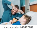 Small photo of grimace dad and son having fun in hospital chamber
