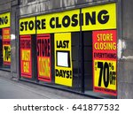Small photo of Large printed signs in a department store window announcing store closing and price reductions.