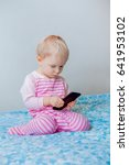 Small photo of Cute adorable white Caucasian blond baby making a call, playing with mobile cell phone with funny expression on face, lifestyle new generation technology, early development