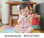 baby girl playing puppet at home | Shutterstock . vector #642107662