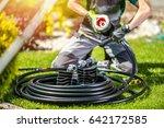 Garden Watering System Building by Professional Garden Systems Technician. Automatic Watering System in the Backyard Garden. - stock photo