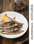 Small photo of Grilled fish capelin or shishamo on white plate