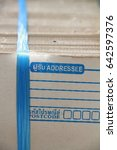 """Small photo of Corrugate cardboard tied with blue plastic rope, mail paper box cardboard, with address blank mark on the right top of lay out, Address from marks in Thai language with """"addressee"""" and """"Zip code."""""""