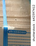 "Small photo of Corrugate cardboard tied with blue plastic rope, mail paper box cardboard, with address blank mark on the right top of lay out, Address from marks in Thai language with ""addressee"" and ""Zip code."""