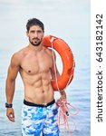 Small photo of Muscular handsome lifeguard man stands on the beach with life raft