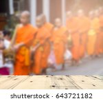 Small photo of wood table and blur image of Morning Alms-Giving in Luang Prabang - Laos
