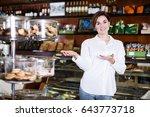 smiling female seller showing... | Shutterstock . vector #643773718