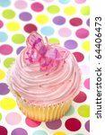 Single cupcake with pink frosting and a butterfly, on polka-dot background. - stock photo