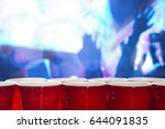 Stock photo plastic red party cups in a row in a nightclub full of people dancing on the dance floor in the 644091835