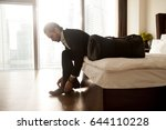 Small photo of Man with luggage puts on shoes on hotel room bed. Young businessman getting ready to go on business trip. Entrepreneur preparing to travel in home bedroom in early morning. Business tourism, vacation