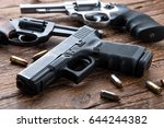 Gun with ammunition on wooden background.