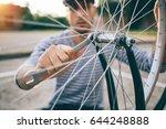 man tightening wheel on bicycle.... | Shutterstock . vector #644248888