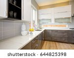 Stock photo luxury kitchen with white quartz natural backsplash natural brown wood cabinets with lots of 644825398