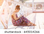 Small photo of Woman writing by pen in notepad at sunny summer
