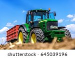 Small photo of Bulgaria, Varna - 18.05.2017 John Deere, beautiful landscape close up of a tractor with a seeder during planting the field. Fluffy clouds in the sky. Concept agro culture.