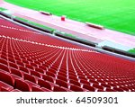 Soccer stadium with red seas and green field - stock photo