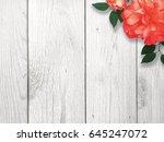 red flower over white wood... | Shutterstock . vector #645247072