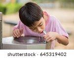 Little asian boy drinking water ...
