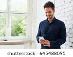 happy young man using his smart ... | Shutterstock . vector #645488095