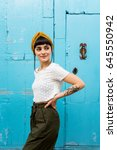 Small photo of Pretty young female tourist posing in front of beautiful wooden door of bright cyan colour in the centre of old mediterranean coastal town, her hairstyle enhanced by turban
