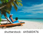 young woman with laptop on beach | Shutterstock . vector #645683476