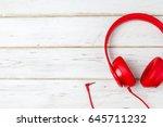red headphones over wood white...   Shutterstock . vector #645711232