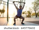 Small photo of workout with suspension straps In the outdoor gym, strong man training early in morning on the park, sunrise or sunset in the sea background