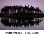 the island is covered with trees among lakes north at sunset. - stock photo