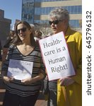 """Small photo of Asheville, North Carolina, USA - February 25, 2017: Women hold signs at an Affordable Care Act rally saying """"Healthcare is a Human Right"""" as Republicans move to repeal Obamacare"""