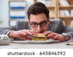 hungry funny businessman eating ... | Shutterstock . vector #645846592