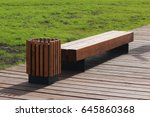 Wooden Bench And Trash Can In...
