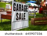 Small photo of Garage sale sign on the shady lawn of a suburban home, shallow focus in center of sign