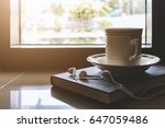 cup of coffee on book by the... | Shutterstock . vector #647059486