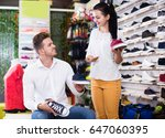 shop assistant helping customer ... | Shutterstock . vector #647060395
